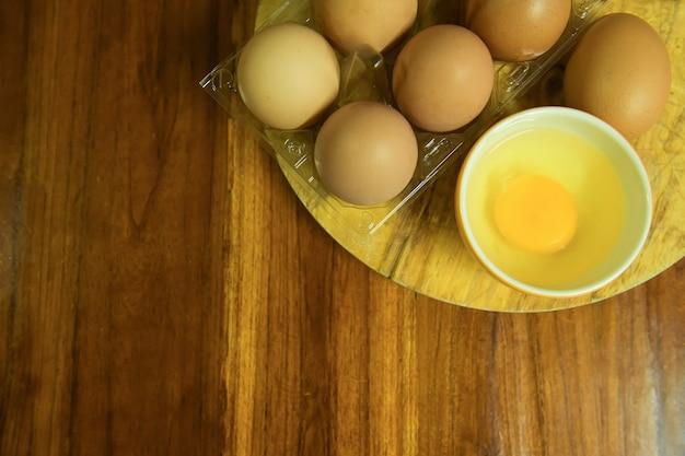 黄色の木製の背景の上の卵ボックスに生の鶏卵の拡大図。
