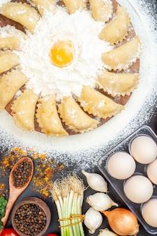小麦粉と黒いテーブルの上の食品のセットと茶色のトレイに生餃子のクローズアップビュー