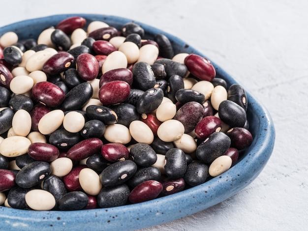 복사 공간이 있는 검정 빨강 및 흰색 콩이 혼합된 회색 콘크리트 배경에 파란색 접시에 있는 원시 혼합 콩의 보기를 닫습니다