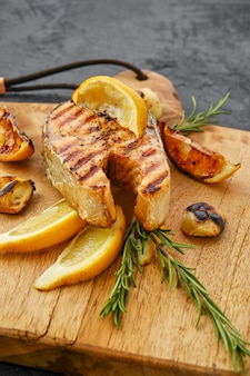 調理の準備ができている木製のまな板上の生のマスステーキのクローズアップビュー