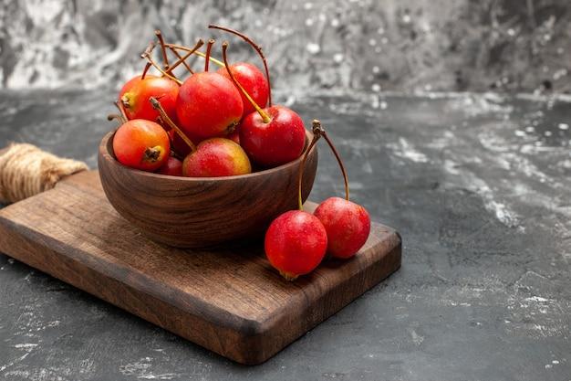 Крупным планом вид красных чери в коричневой миске и на небольшой разделочной доске на сером