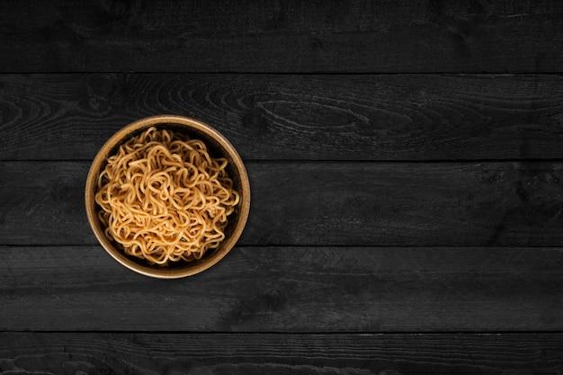 Крупным планом вид рисовой лапши, изолированной на черном деревянном столе.
