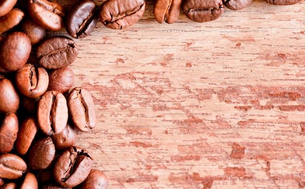 Крупным планом вид жареных кофейных зерен, старый деревянный фон