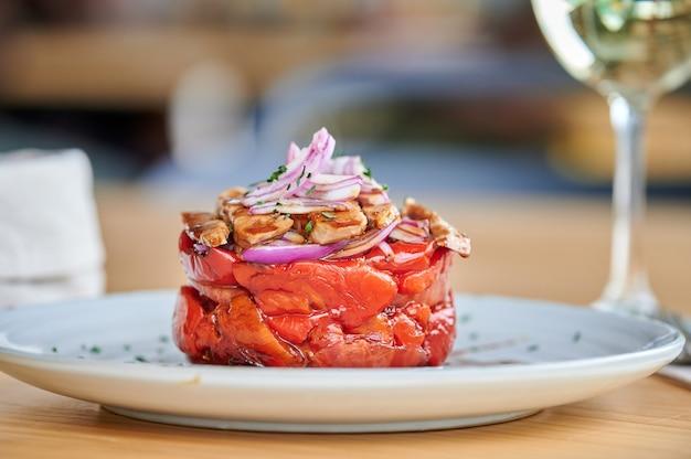 Крупным планом вид салата из жареного красного болгарского перца с тунцом и красным луком в реальной обстановке