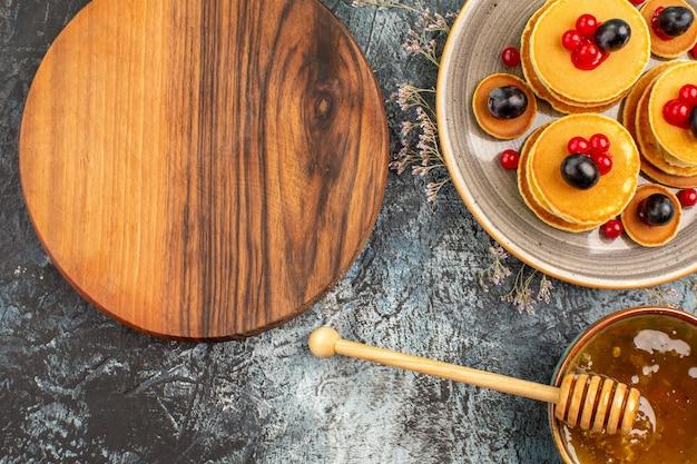 둥근 나무 커팅 보드 과일 팬케이크와 달콤한 꿀의 뷰를 닫습니다