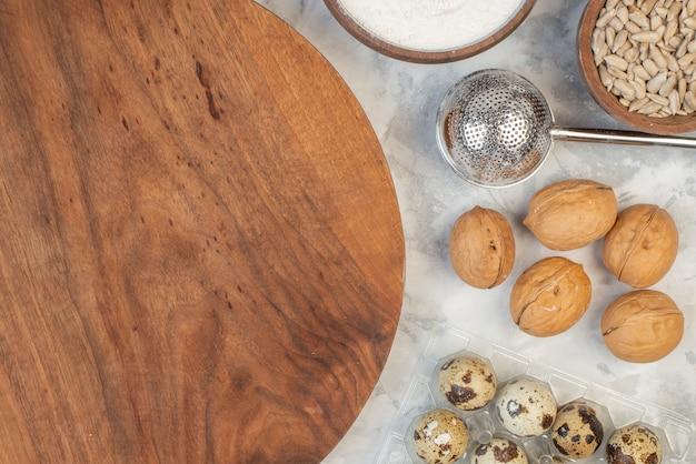 Крупным планом вид овса на круглой деревянной разделочной доске в коричневой миске, яйца, грецкие орехи, сахар на фоне льда