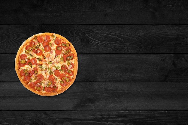 Крупным планом вид округлой пиццы, изолированной на черном деревянном столе.