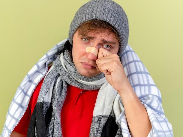 Крупным планом вид грустного молодого красивого светловолосого больного человека в зимней шапке и шарфе, завернутом в плед, смотрящего вперед, вытирая слезу пластырем на носу, изолированном на оливково-зеленой стене