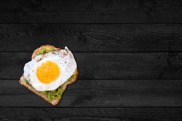 Крупным планом вид сэндвич с жареным яйцом на черном деревянном столе.