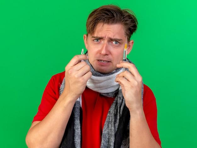 주사기와 녹색 벽에 고립 된 의료 앰플을 들고 스카프를 입고 무서 워 젊은 잘 생긴 금발 아픈 남자의 근접 촬영보기