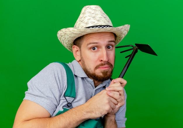 Крупным планом вид испуганного молодого красивого славянского садовника в униформе и шляпе, держащего грабли, изолированного на зеленой стене