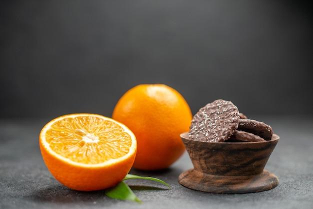 Крупным планом вид целых и разрезанных пополам свежих апельсинов и печенья на темном столе