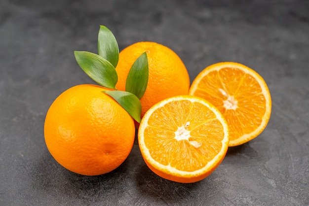 暗いテーブルの上の黄色の全体とみじん切りのオレンジのセットのクローズアップビュー