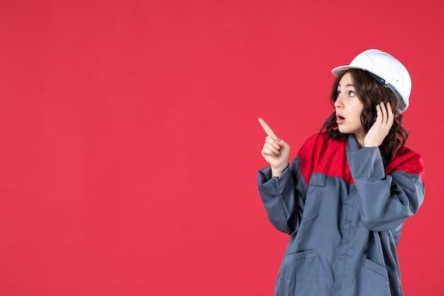 Крупным планом вид потрясенной женщины-строителя в униформе с каской, указывающей что-то справа на изолированной красной стене