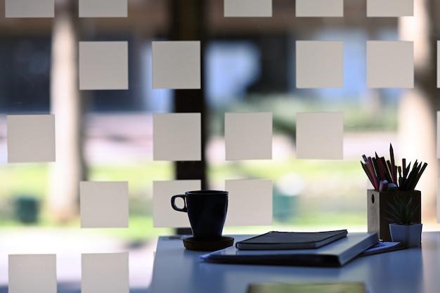 白いテーブルの上のコーヒーカップ、ノートブック、植物と窓の近くのシンプルなワークスペースのビューを閉じます。