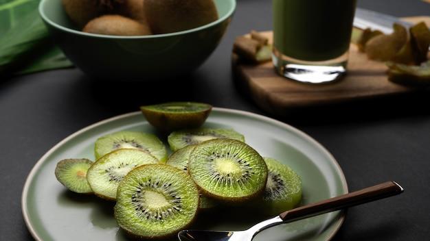 プレート上のスライスした新鮮なキウイフルーツとキッチンテーブルの上のガラスの健康的な新鮮なキウイスムージーのクローズアップビュー