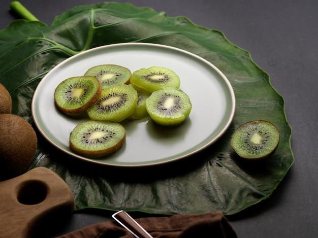 キッチンテーブルの緑の葉で飾られたプレート上のスライスされた新鮮なキウイフルーツのクローズアップビュー