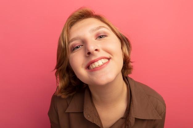 ピンクの壁に孤立して見える笑顔の若いブロンドの女の子の拡大図