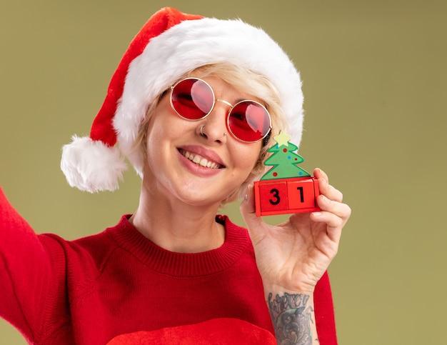 クリスマス帽子とサンタ クロース クリスマス セーターを着た笑顔の若いブロンドの女性のクローズ アップ ビュー オリーブ グリーンの壁に孤立した探している日付でクリスマス ツリーのおもちゃを保持している眼鏡をかけた