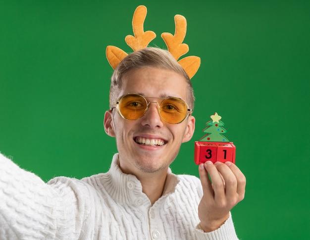 緑の壁に孤立したカメラに向かって手を伸ばす日付でクリスマス ツリーのおもちゃを保持しているメガネでトナカイの角のヘッドバンドを着て笑顔の若いハンサムな男のクローズ アップ ビュー