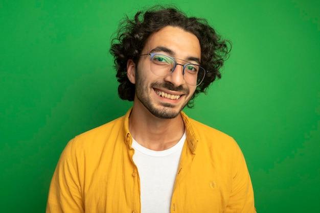 녹색 벽에 고립 된 전면을보고 안경을 쓰고 웃는 젊은 잘 생긴 남자의 근접 촬영보기