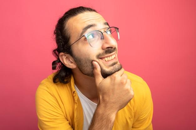 분홍색 벽에 고립 된 측면을보고 턱을 만지고 안경을 쓰고 웃는 젊은 잘 생긴 남자의 근접 촬영보기