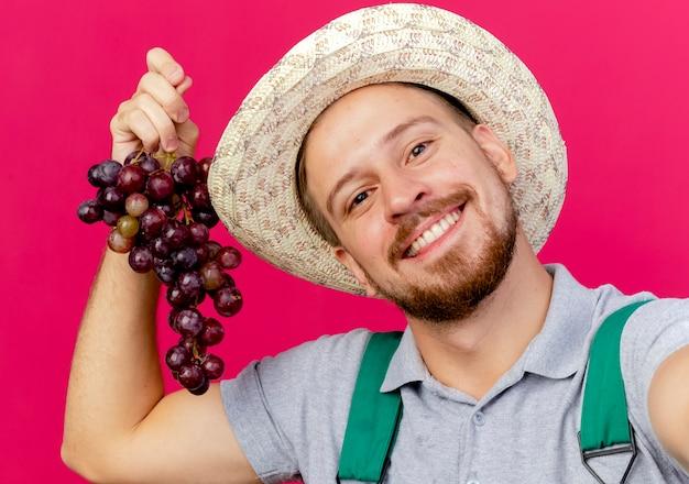 Крупным планом вид улыбающегося молодого красивого славянского садовника в униформе и шляпе, держащего виноград