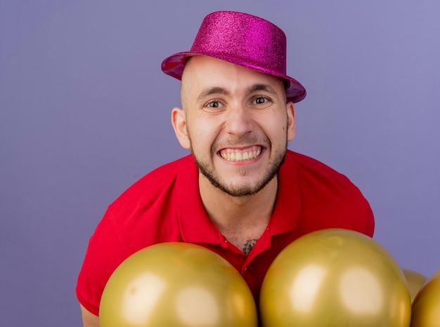 Крупным планом вид улыбающегося молодого красивого славянского тусовщика в партийной шляпе, стоящего за воздушными шарами, смотрящего в камеру, изолированного на фиолетовом фоне