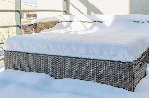 寒い冬の日に雪に覆われた合成プラスチック籐とガラスの庭の家具のビューを閉じます。ガーデンファニチャーのメンテナンスのコンセプト。