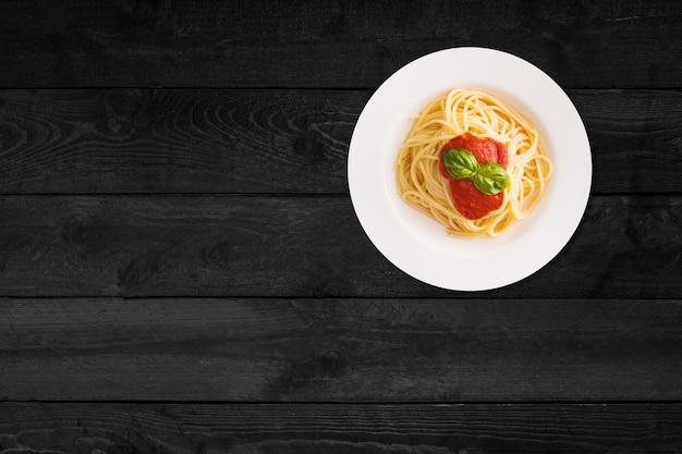 Крупным планом вид спагетти с кетчупом, изолированных на черном деревянном столе.
