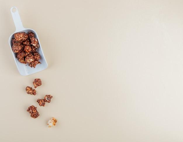 コピースペースと左側と白の背景にチョコレートポップコーンのスプーン1杯のクローズアップビュー
