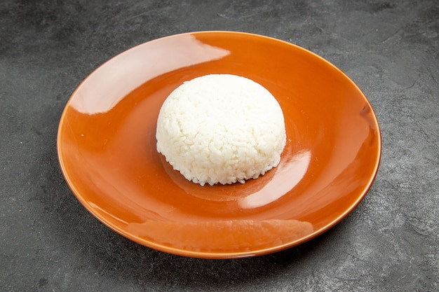 어둠에 갈색 접시에 찐 쌀 식사의보기를 닫습니다