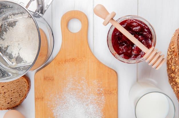 Крупным планом вид клубничного варенья в банку муки ломтик ржаного хлеба стакан молока и разделочную доску на деревянной поверхности