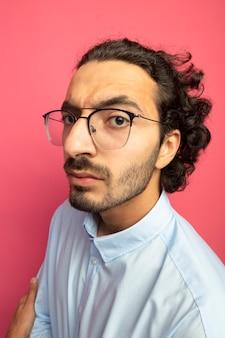 진홍색 벽에 고립 된 프로필보기에 서 안경을 쓰고 엄격한 젊은 잘 생긴 백인 남자의 근접 촬영보기
