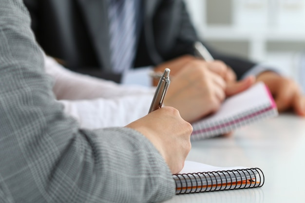 Крупным планом вид студентов или бизнесменов вручает что-то писать во время конференции. деловая встреча, ведение блога или концепция профессионального образования