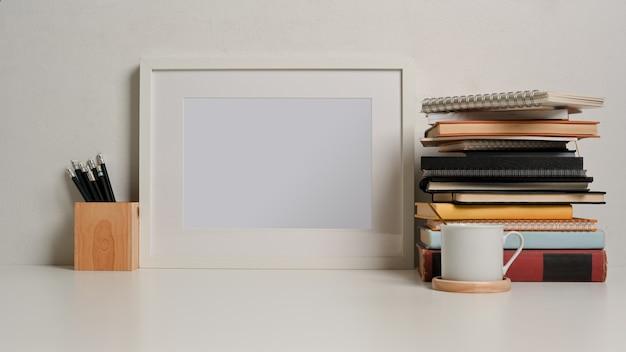Крупным планом вид учебного стола с макетом рамки стопки книжных карандашей