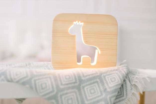 Крупным планом вид стильной деревянной ночной лампы с изображением жирафа на сером одеяле в уютном светлом интерьере спальни.