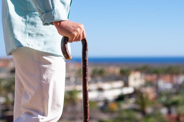지팡이의 도움으로 걷는 고통받는 노인의 클로즈업보기. 물 위에 수평선