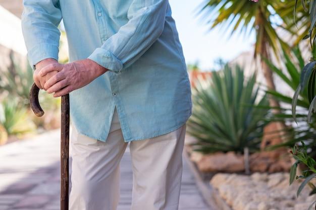 지팡이의 도움으로 걷는 고통받는 노인의 클로즈업 보기.