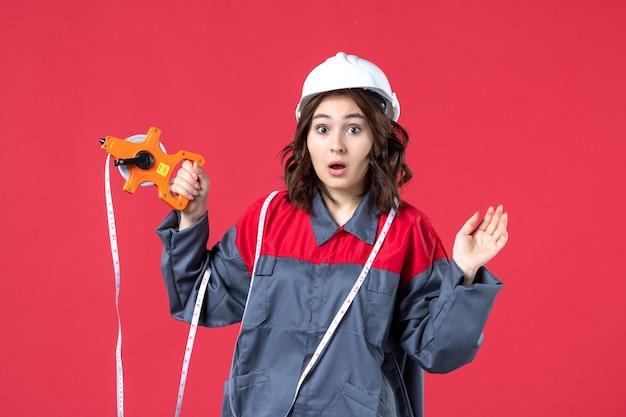 붉은 벽에 테이프를 측정하는 하드 모자를 쓰고 제복을 입은 놀란 여성 건축가의 뷰를 닫습니다