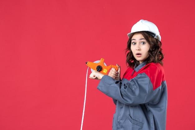 붉은 벽에 측정 테이프를 사용하여 하드 모자와 제복을 입은 놀란 여성 건축가의 뷰를 닫습니다