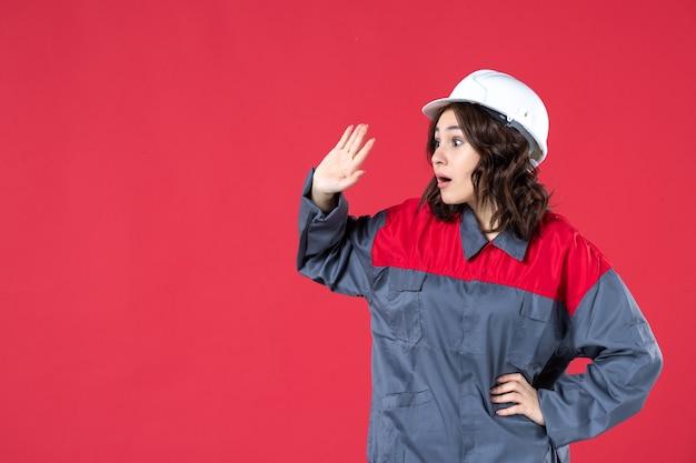 하드 모자와 제복을 입은 놀란 여성 빌더의 뷰를 닫고 고립 된 붉은 벽에 뭔가에 집중