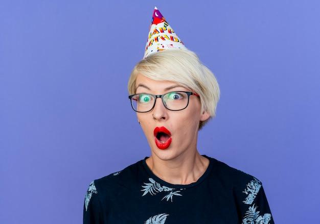 복사 공간이 보라색 배경에 고립 된 카메라를보고 안경과 생일 모자를 쓰고 놀란 젊은 금발 파티 소녀의 근접 촬영보기