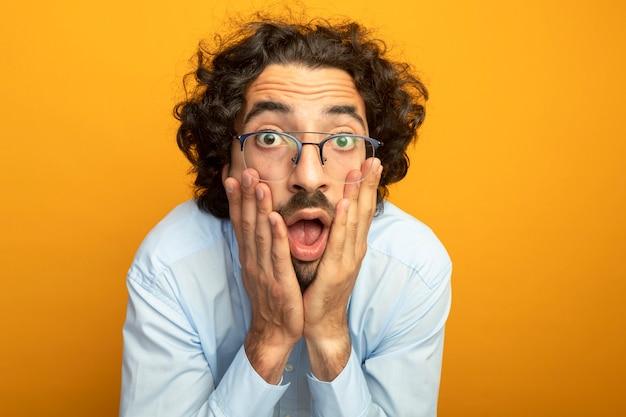 Крупным планом вид удивленного молодого красивого человека в очках, положившего руки на лицо, смотрящего вперед, изолированного на оранжевой стене