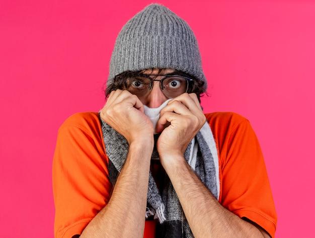 안경 겨울 모자와 스카프 입을 덮고 놀란 젊은 아픈 남자의 근접 촬영보기 분홍색 벽에 고립 된 전면을보고 그것에 손을 댔을 스카프