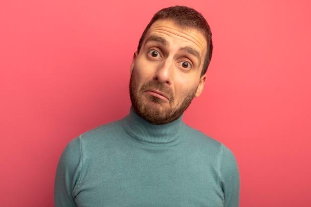 분홍색 벽에 고립 된 앞을보고 놀란 된 젊은 남자의 근접 촬영보기