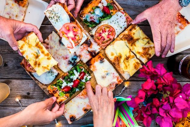 イタリアのピザを取り、お祝いパーティーのために友情で一緒に食べる白人グループの人々の手でいっぱいのテーブルのクローズアップビュー