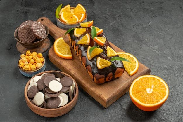 어두운 테이블에 커팅 보드에 비스킷으로 오렌지를 잘라 맛있는 케이크의 뷰를 닫습니다.