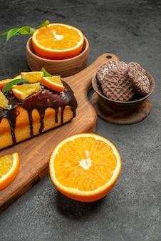 Крупным планом вид вкусных тортов нарезанных апельсинов с печеньем на разделочной доске на темном столе