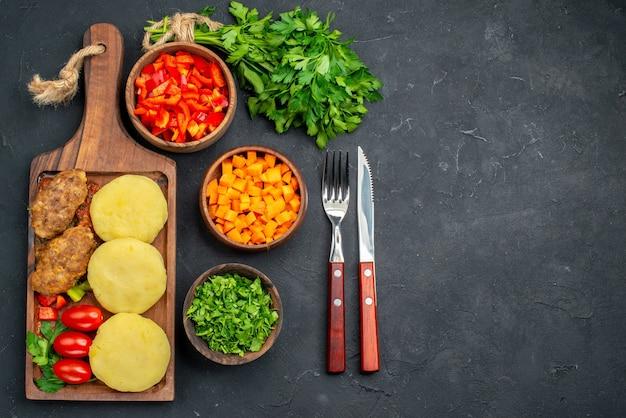 Крупным планом вид вкусной котлетной еды с зелеными нарезанными овощами на ужин с перцем и кетчупом